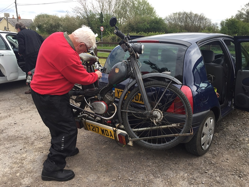 "Dennis mounting the ""mother of all mopeds"" on the back of his car - his ""NSU Quickly"" which Dennis has owned for 50 years !!  To describe it as in ""original condition"" would be kindest but although Dennis does not make it look beautiful he does conscientiously maintain it !"